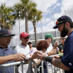 Boston Red Sox's Mike Napoli, right, signs autographs for fans after a workout Monday at spring training in Fort Myers Fla.  The Associated Press