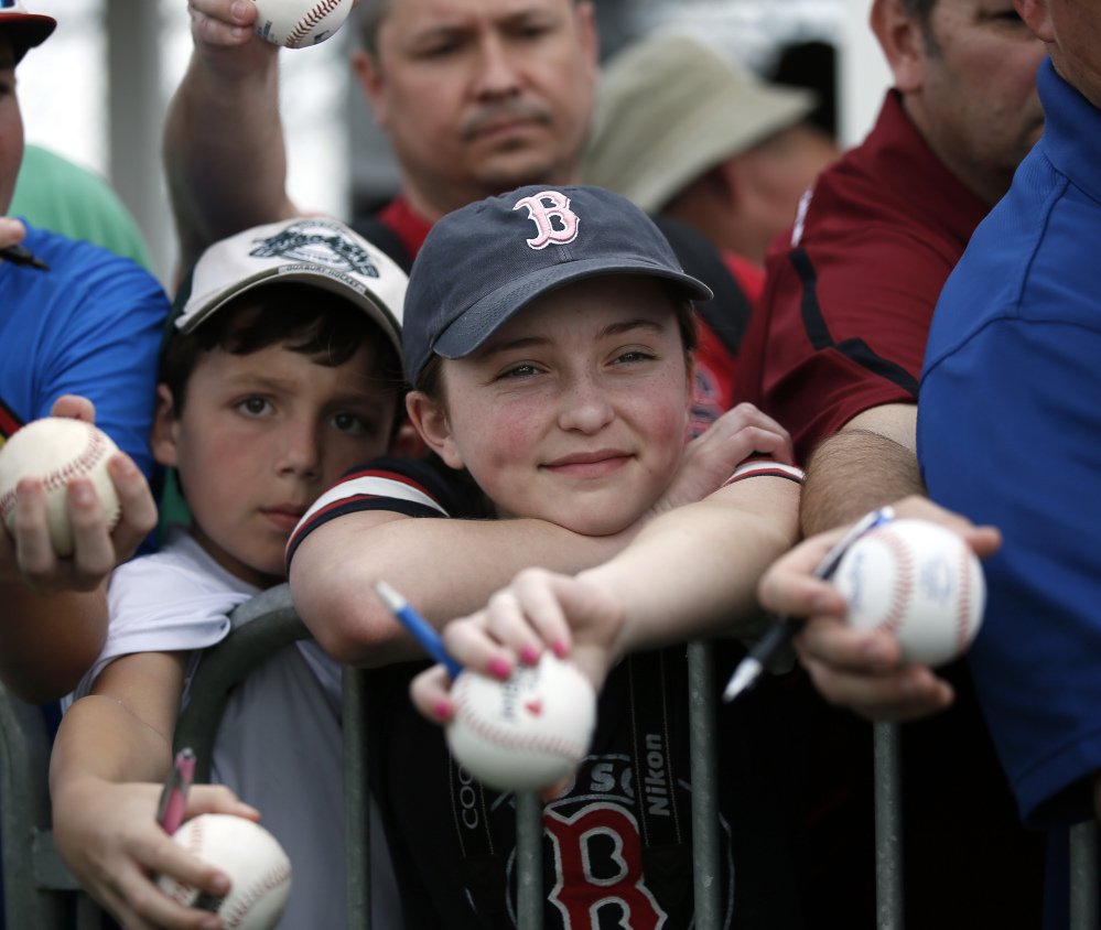Reece Pearlman of Framingham, Mass., center, smiles as he waits for Mike Napoli to sign an autograph after a workout Monday in Fort Myers. Napoli has reason to smile too after offseason surgery for a severe case of  obstructive sleep apnea.
