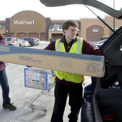 Thomas Bailey, right, a Wal-Mart employee at the company's Scarborough store, assists customer Theresa Graham of Windham with a purchase Tuesday. Bailey, who trains fellow Wal-Mart workers, says it has been fun to share the news of the pay increase with new hires.