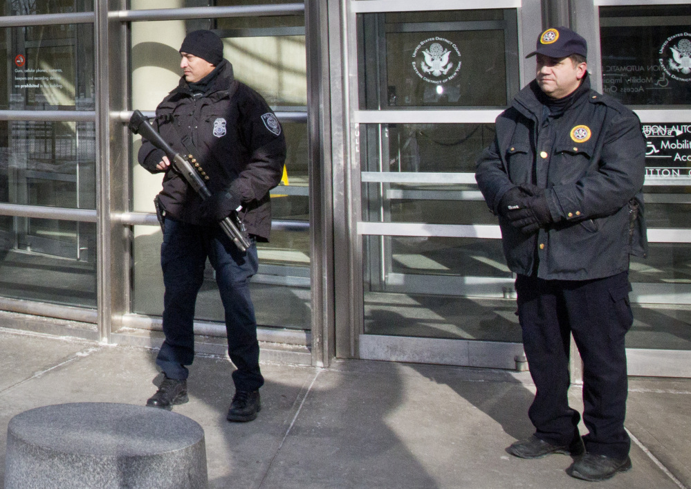 A Homeland Security police officer, left, joins a federal court policeman as security is enhanced during the arraignment of two men on terrorism related charges Wednesday in Brooklyn, N.Y. The men were arrested along with a third man Wednesday on charges of plotting to travel to Syria to join the Islamic State group and wage war against the U.S.