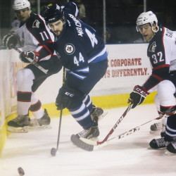 St. John's defender Julian Melchiori scrambles to get the puck away from Francis Wathier, left, and Tyler Gaudet, of the Pirates Wednesday night at the Cross Insurance Arena in Portland.