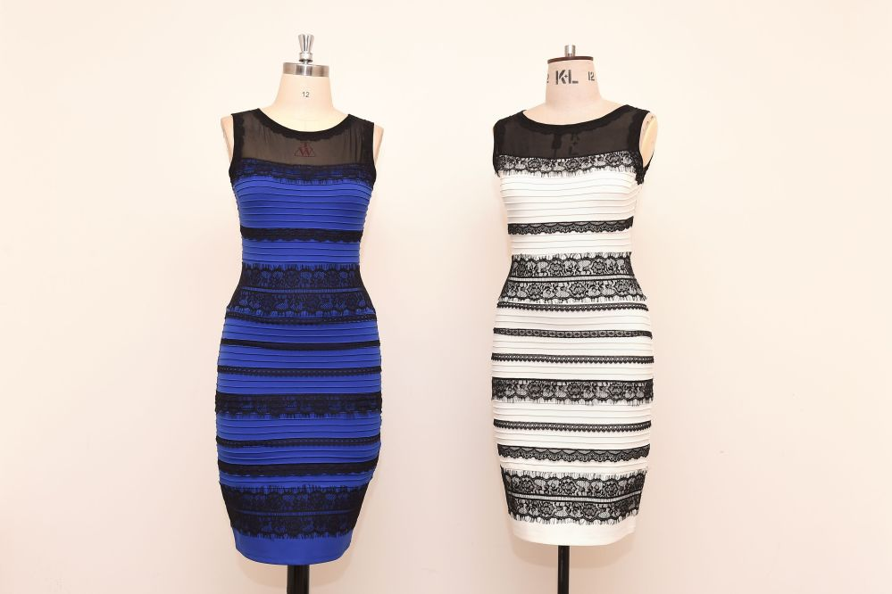The royal blue and black dress, left,  alongside an ivory and black version, made by Roman Originals, that has sparked a global debate on Twitter over its true colour is on display in Birmingham, England, on Friday.