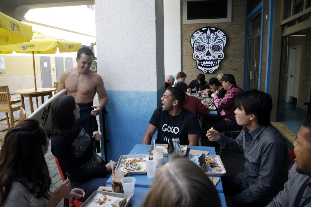 Nathan Seymour, top left, with a surfboard, chats with his friends at U.S. Taco Co., which is owned by Taco Bell, in Huntington Beach, Calif. The Associated Press