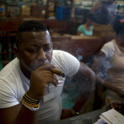 "Quality control employee Manuel Lamoth, 30, smokes a cigar at the Corona cigar factory in Havana, Cuba, Thursday. Cuban cigar makers are happy with new U.S. rules that let more Americans travel to the island and legally bring back as much as $100 worth of cigars for the first time in decades. Officials said during this week's annual cigar festival that this year alone, they expect to double sales of hand-rolled ""habanos"" on the island. The Associated Press"
