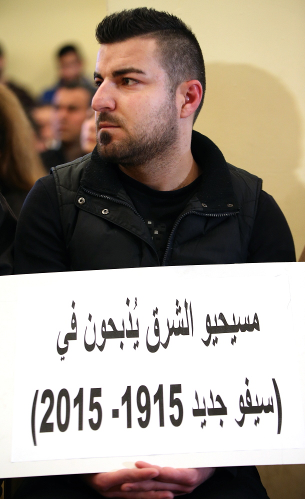"""A man whose relatives were abducted in Syria participates in a sit-in in Beirut. His placard reads, """"The Christians of the east are being slaughtered in a new massacre."""""""