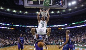 Celtics guard Avery Bradley hangs from the rim after slamming a dunk against the Charlotte Hornets in the second half of Friday night's game in Boston. The Celtics defeated the Hornets, 106-98, after trailing by 16 points in the third quarter.