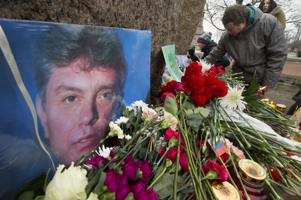 People lay flowers in memory of Boris Nemtsov, seen at left, at the monument of political prisoners 'Solovetsky Stone' in central St. Petersburg, Russia, Saturday.