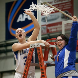 Nia Irving celebrates with team manager Kellie Goldsmith, right, while cutting the net after Lawrence beat Thornton Academy to capture the Class A State Champioship. Derek Davis/Staff Photographer