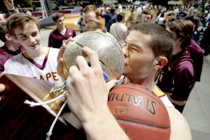 FEB. 27 FINALS: Cape Elizabeth's Justin Guerette kisses the gold ball after the Capers beat Medomak Valley in the Class B boys' state championship game at the Cross Insurance Arena in Portland.