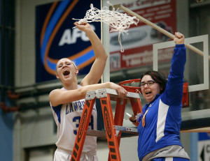 Nia Irving celebrates with team manager Kellie Goldsmith, right, while cutting the net after Lawrence beat Thornton Academy to capture the Class A State Championship. Derek Davis/Staff Photographer
