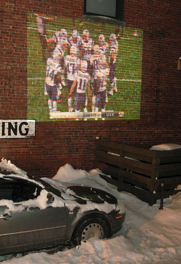 The Super Bowl is projected onto a brick wall for viewing at The Thirsty Pig where seating was built out of snow Sunday. Jill Brady/Staff Photographer