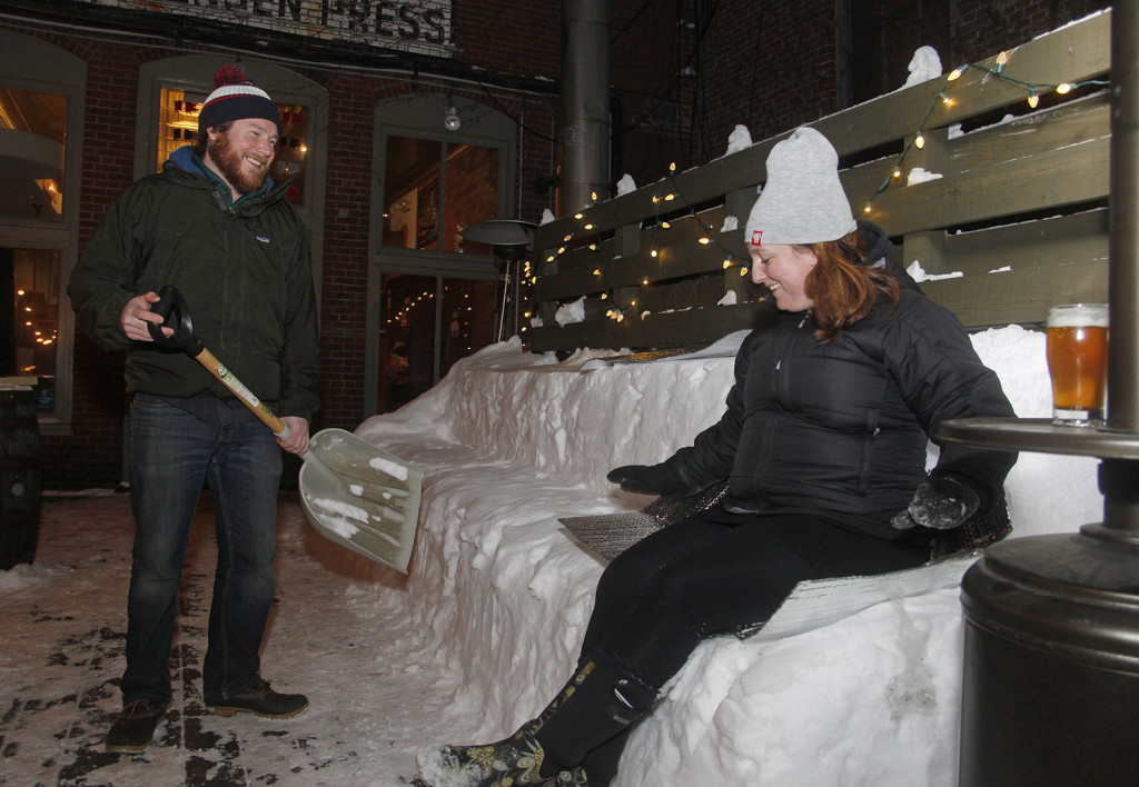 Trevor Fischer, a bartender at The Thirsty Pig, watches as Margaret Keilty of South Portland tries out the seating he made out of snow where patrons were invited to watch the  Super Bowl projected on a neighboring brick wall  Sunday. Jill Brady/Staff Photographer