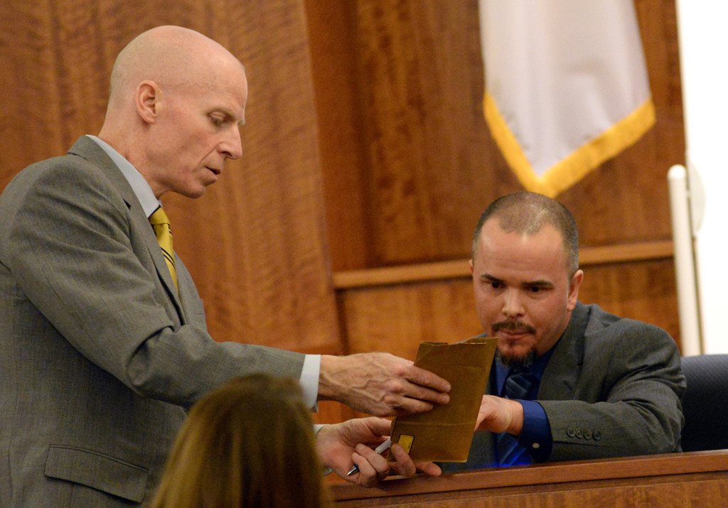 Assistant District Attorney William McCauley, left, shows former Massachusetts State Police officer Edward Reece an evidence bag containing shell casings Reece marked as he testifies during the murder trial of Aaron Hernandez. The Associated Press
