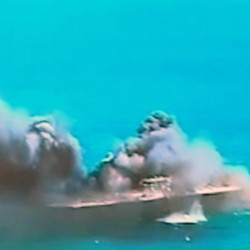 "Smoke billows from a mock U.S. aircraft carrier during large-scale naval and air defense drills by Iran's Revolutionary Guard near the Strait of Hormuz on Wednesday. Cmdr. Kevin Stephens, spokesman for the U.S. Navy's 5th Fleet in Bahrain, said they were monitoring the drills, but downplayed the simulated attack on the carrier, saying the U.S. military was ""not concerned about this exercise."" The Associated Press"