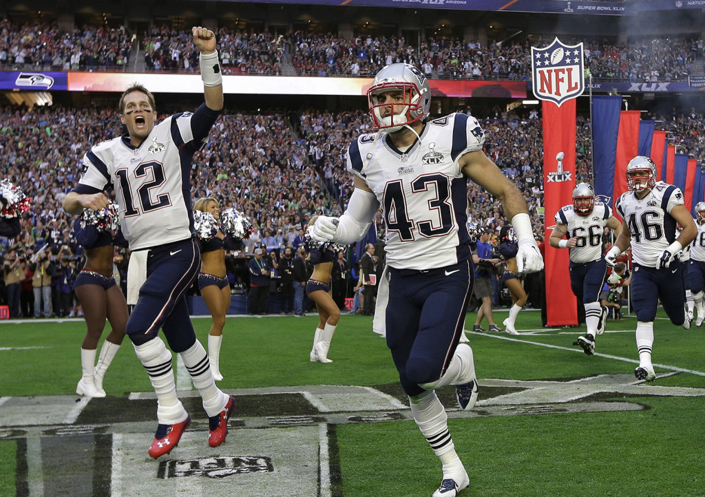 New England Patriots quarterback Tom Brady (12) and defensive back Nate Ebner (43) run  onto the field before the NFL Super Bowl XLIX football game against the Seattle Seahawks Sunday. The Associated Press