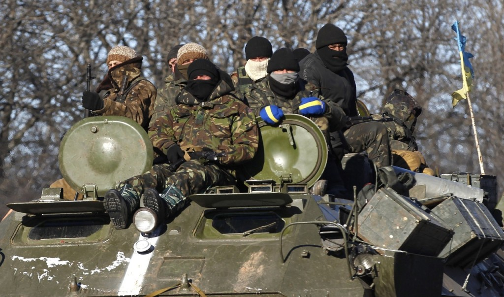 Ukrainian government soldiers sit atop an armored vehicle driving on a road between the town of Artemivsk, Ukraine, toward Debaltseve Tuesday before withdrawing from  the strategic city on Wednesday.  The Associated Press