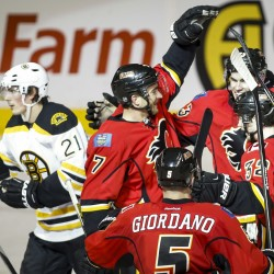 Bruins Loui Eriksson, left, skates away as Flames TJ Brodie, center left, celebrates his game-winning goal with teammates during overtime in Calgary, Alberta on Monday. The Associated Press