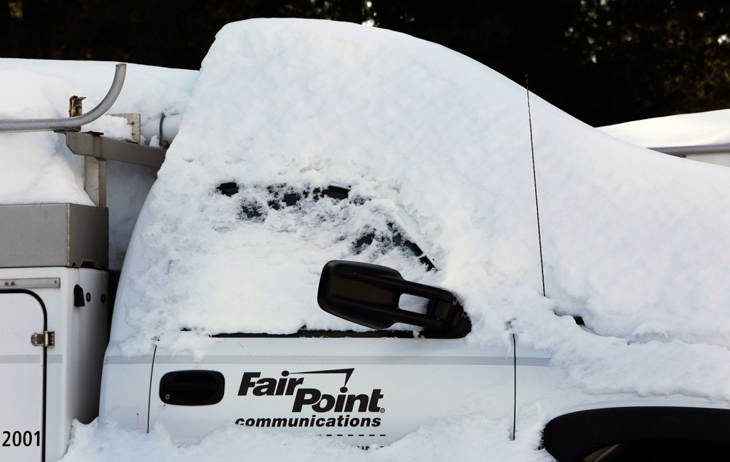 A FairPoint truck is covered in snow at one of the company's offices in February 2015 in Concord, N.H.