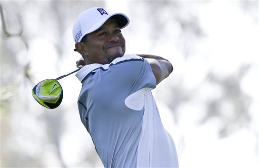 Tiger Woods watches his tee shot head far to the right on the 11th hole at Torrey Pines in San Diego during the first round of the Farmers Insurance Open golf tournament Thursday. He left the tournament with a stiff back. The Associated Press
