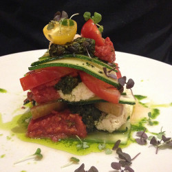 A raw vegan lasagna prepared by chef Matthew Kenney in Miami Beach. The lasagna is layered with zucchini, tomatoes, macadamia ricotta, spicy marinara, pistachio pesto and olive oil.