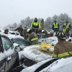 Hermon Fire Capt. Chandler Corriveau, who also is a full-time firefighter with the Bangor Fire Department, center rear, helps direct firefighters, troopers and other first responders to check on the many motorists still inside their wrecked vehicles during the multi-vehicle pileup outside of Bangor on Wednesday.