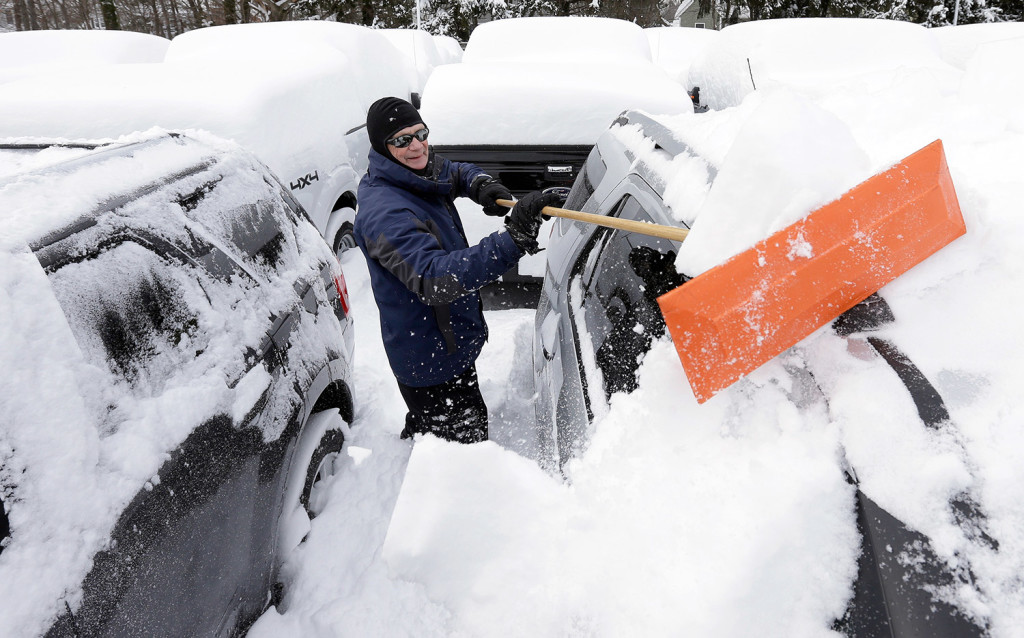 Lealand Welsh, of Wrentham, Mass., removes snow from cars and trucks at a Ford dealership in Norwood, Mass.