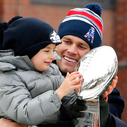 New England Patriots quarterback Tom Brady looks on as his son, Benjamin admires the Vince Lombardi Trophy during a parade in Boston, Wednesday. The Associated Press