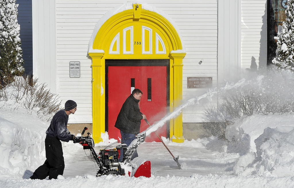 FEB. 3: Rodney Burns, facilities director for My Place Teen Center in Westbrook, uses a snowblower to clear snow Tuesday morning with the help of youth worker Anthony Moore.  Gordon Chibroski / Staff Photographer
