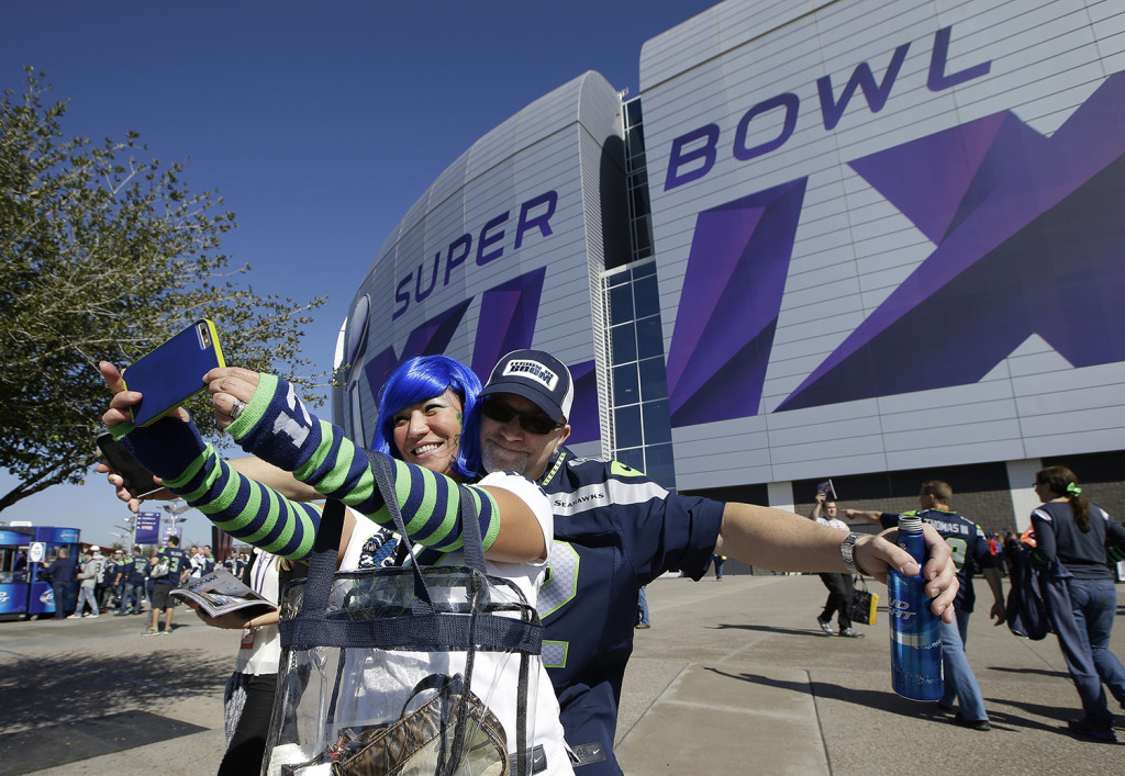 Seattle Seahawks fans Sooji and Mike Hartzell pose for photos outside of University of Phoenix Stadium before the NFL Super Bowl XLIX football game between the Seahawks and the New England Patriots on Sunday. The Associated Press