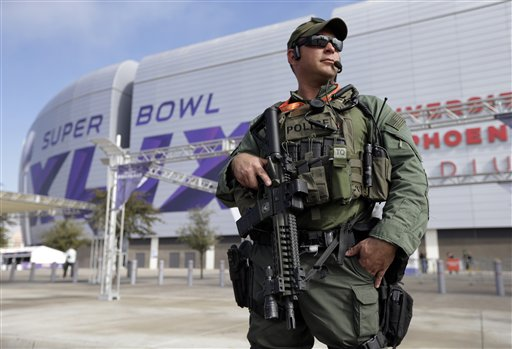 A police guard stands outside of University of Phoenix Stadium before Sunday's Super Bowl. The Associated Press