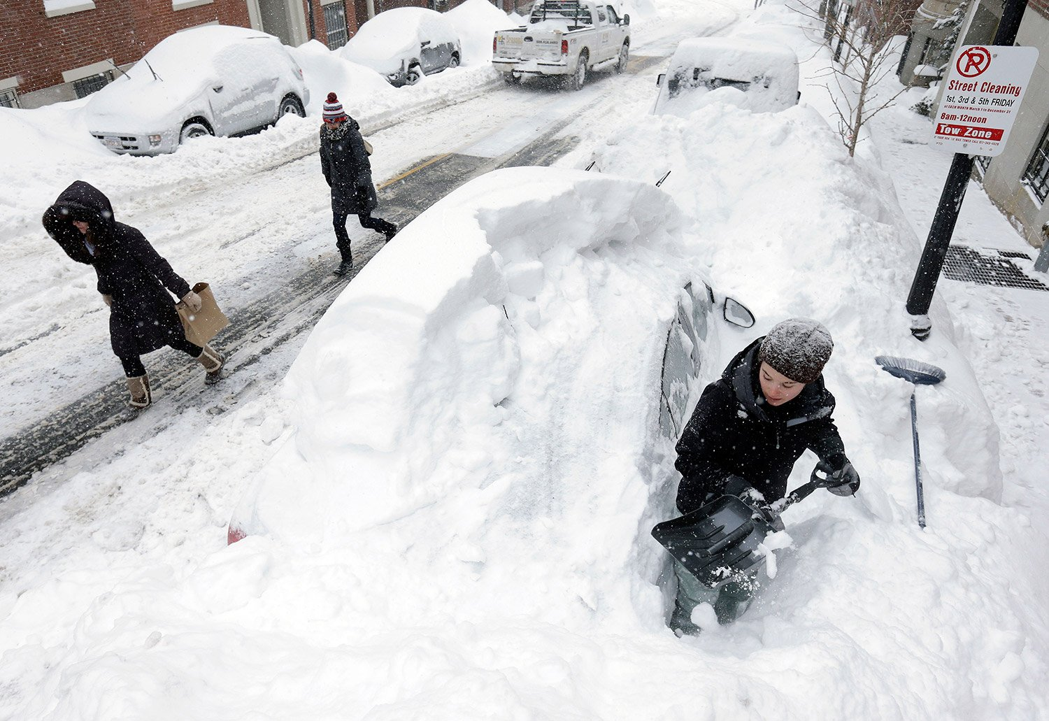 Taylor LaBrecque digs her car out of a snow pile on Beacon Hill Feb. 9, 2015 in Boston. A long winter storm that began Saturday night remained in effect for a large swath of southern New England until the early morning hours Tuesday.