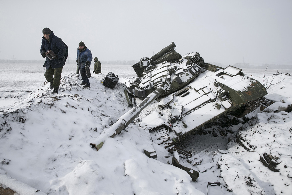 Members of the separatist self-proclaimed Donetsk People's Republic army collect parts of a destroyed Ukrainian army tank in the town of Vuhlehirsk, about 6 miles to the west of Debaltseve, on Monday. Reuters
