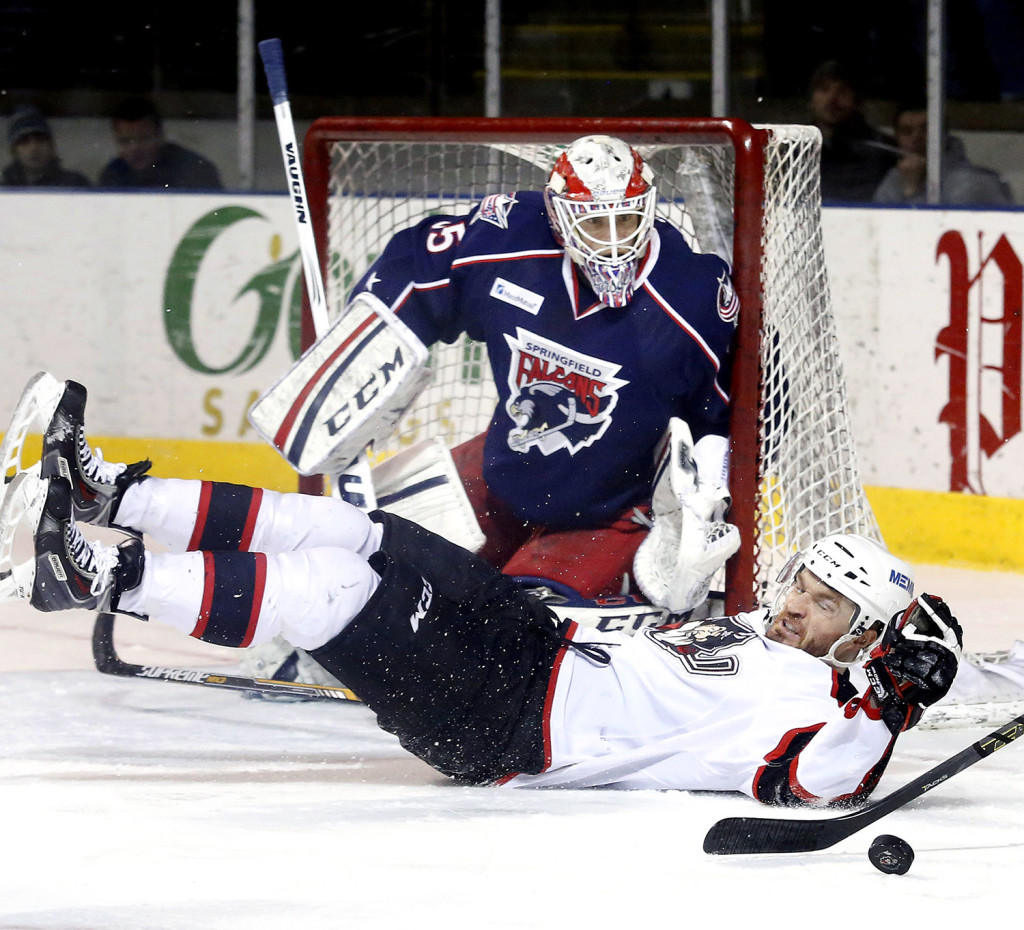 Anton Forsberg of Springfield keeps his eyes on the puck as Alex Bolduc of Portland is tripped in front of the net during the first period Sunday. Derek Davis/Staff Photographer