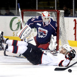 Anton Forsberg of Springfield keeps his eyes on the puck as Alex Bolduc of Portland is tripped in front of the net during the first period. Derek Davis/Staff Photographer