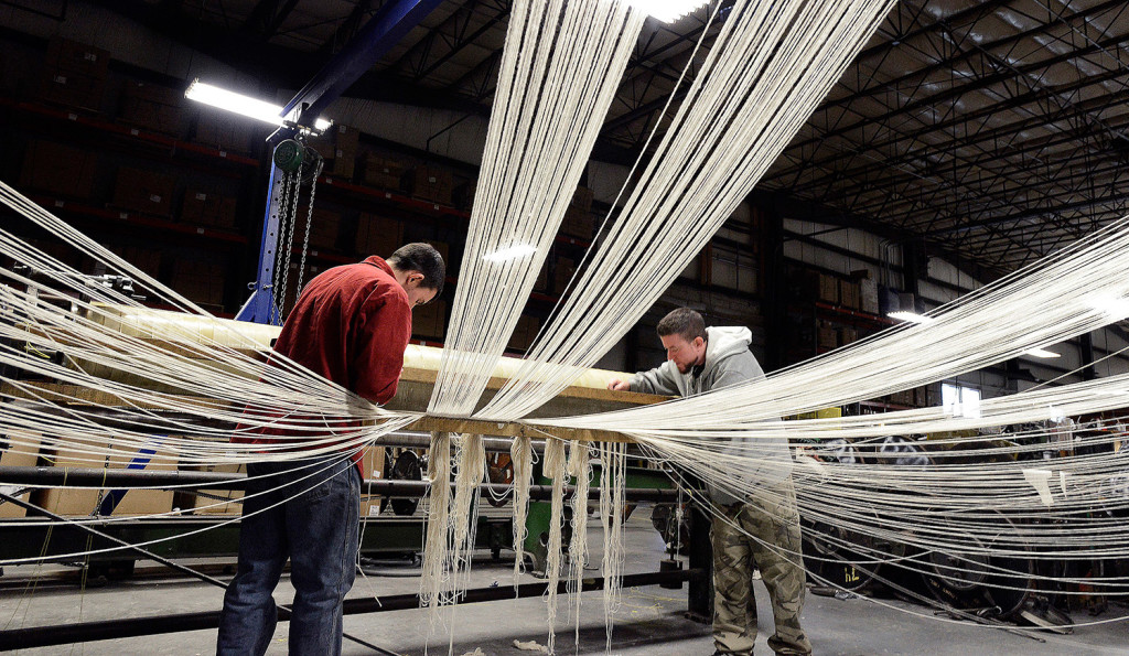 Nick Krueger and Patrick Kirby work in the warping department attaching cotton yarn from creels to a warp beam that will be used on a loom at Brahm's Mount Mill.