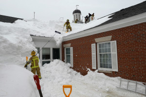 Firefighters from Ogunquit and Wells shovel snow off the Wells Public Library roof Thursday that is partially bowed under the weight.
