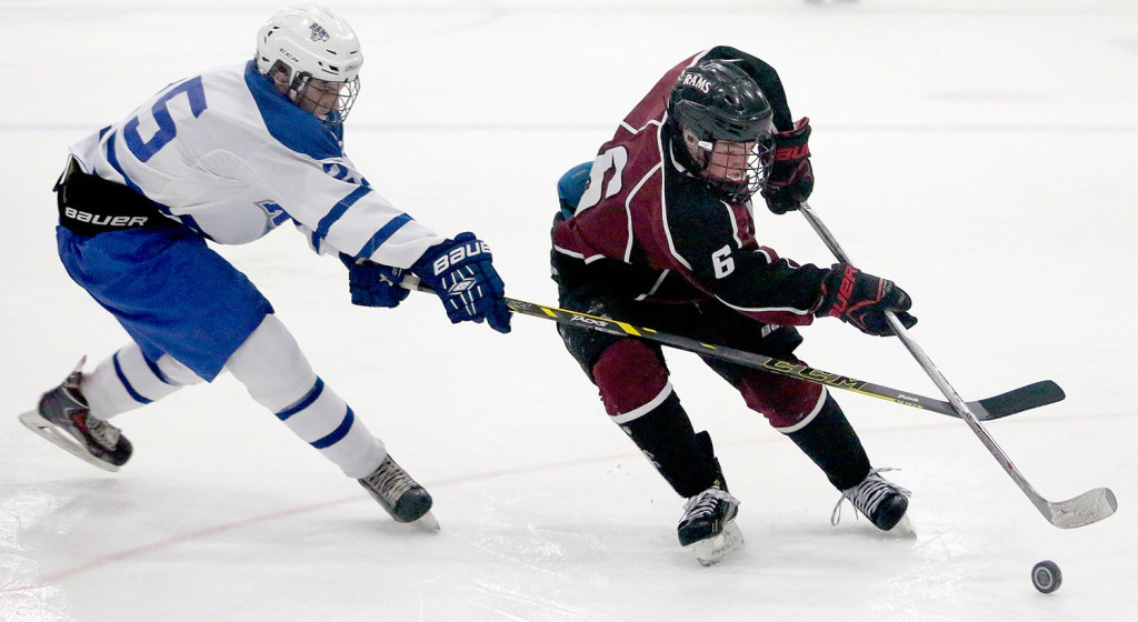 MARCH 4 FINAL: Kennebunk's Kyle Mooney tries to steal the puck from Gorham's Lucas Roop during Wednesday night's Western Class B boys' hockey final at the Androscoggin Bank Colisee in Lewiston.