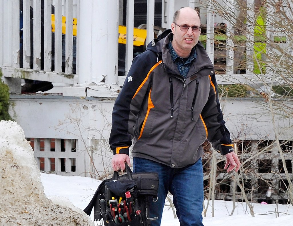 Owner Gregory Nisbet carries tools for an electrical crew from his building at 188 Dartmouth St. in Portland prior to an inspection Tuesday.