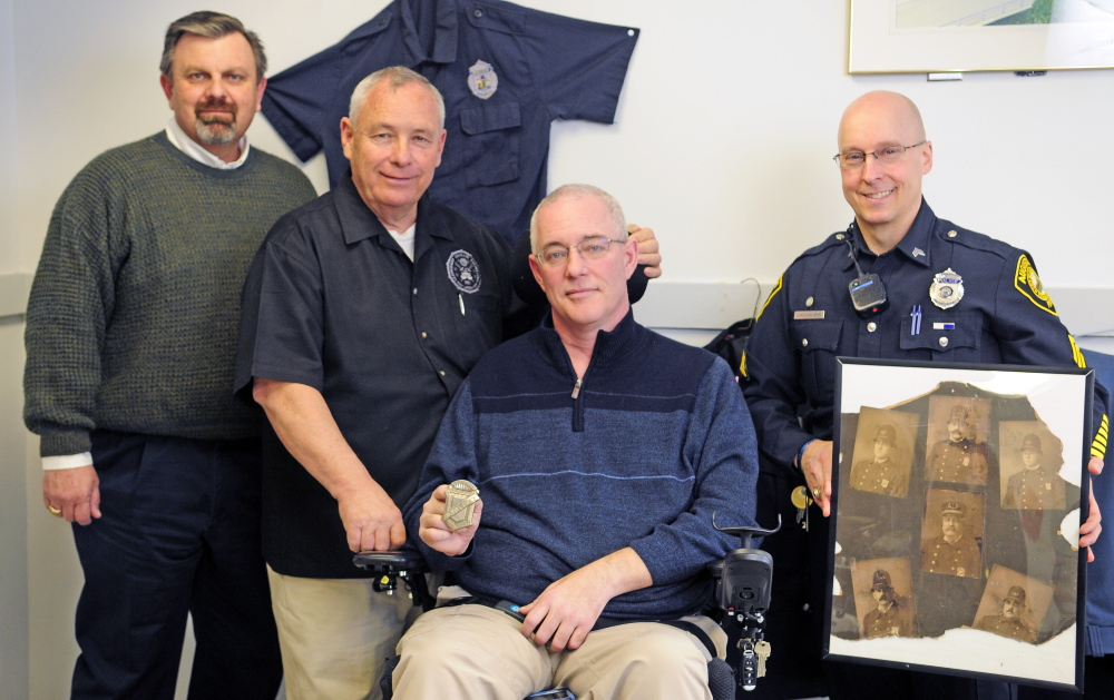 Keith Bushey, second from left, gave the Augusta Police Department an old city marshal's badge, held by Chief Robert Gregoire, third from left, on Wednesday. Also in the photo are David Allen, far left, and Augusta police Sgt. Christian Behr.