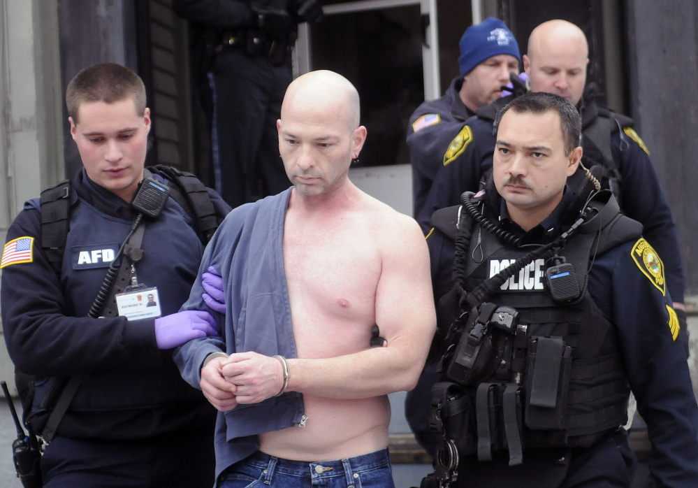 Augusta police and firefighters escort Lorne Sherwood from his apartment at 388 Water St. in Augusta in December. Sherwood pleaded guilty Thursday to assault and terrorizing charges related to a December attack on a neighbor.