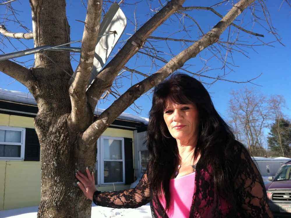 Rhonda West stands by the tree in her Oakland yard where she was attacked by a stray cat.