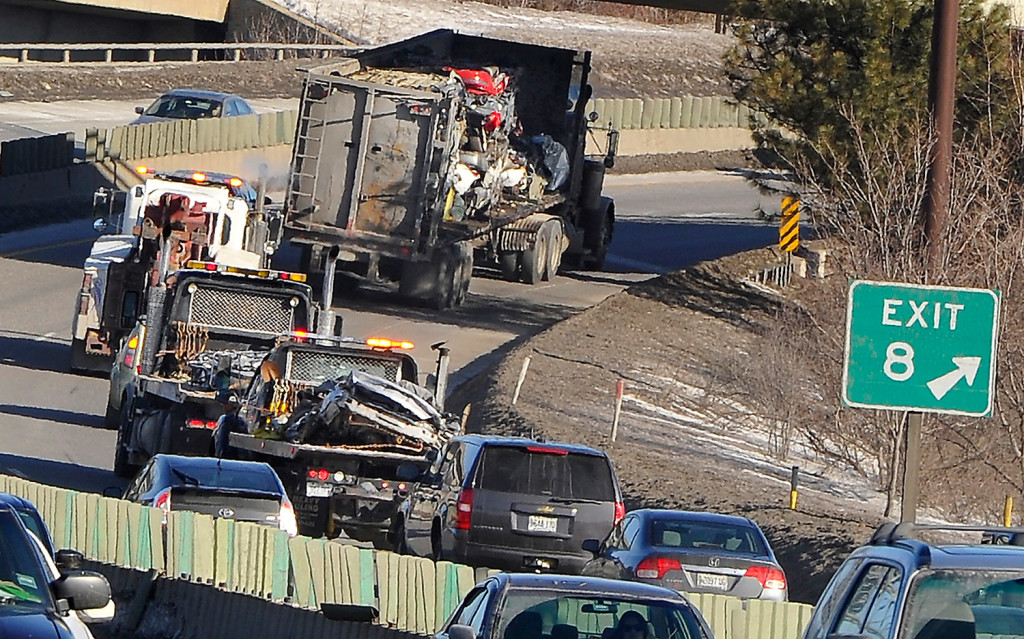 Traffic backed up for miles Friday morning after a tractor-trailer hauling crushed cars spilled part of its load onto Interstate 295 in Portland. The truck is seen here leaving the scene after the flattened cars were loaded onto two flatbed trucks following the carrier.
