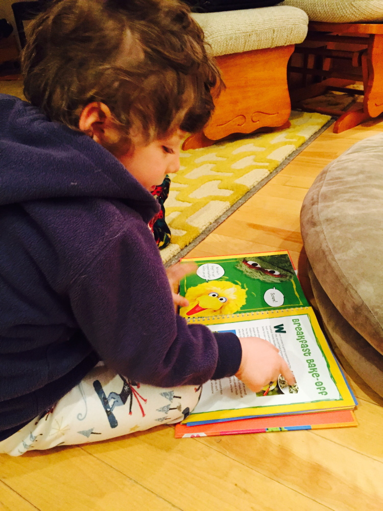 """The author's son, Theo, pores over """"B is for Baking"""" by Susan McQuillan."""