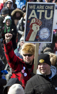 "Marc LeClair of Wausau, Wis., with sign, marches against a ""right-to-work"" proposal on Saturday."