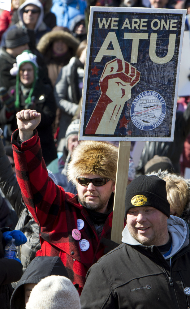 """Marc LeClair of Wausau, Wis., with sign, marches against a """"right-to-work"""" proposal on Saturday."""
