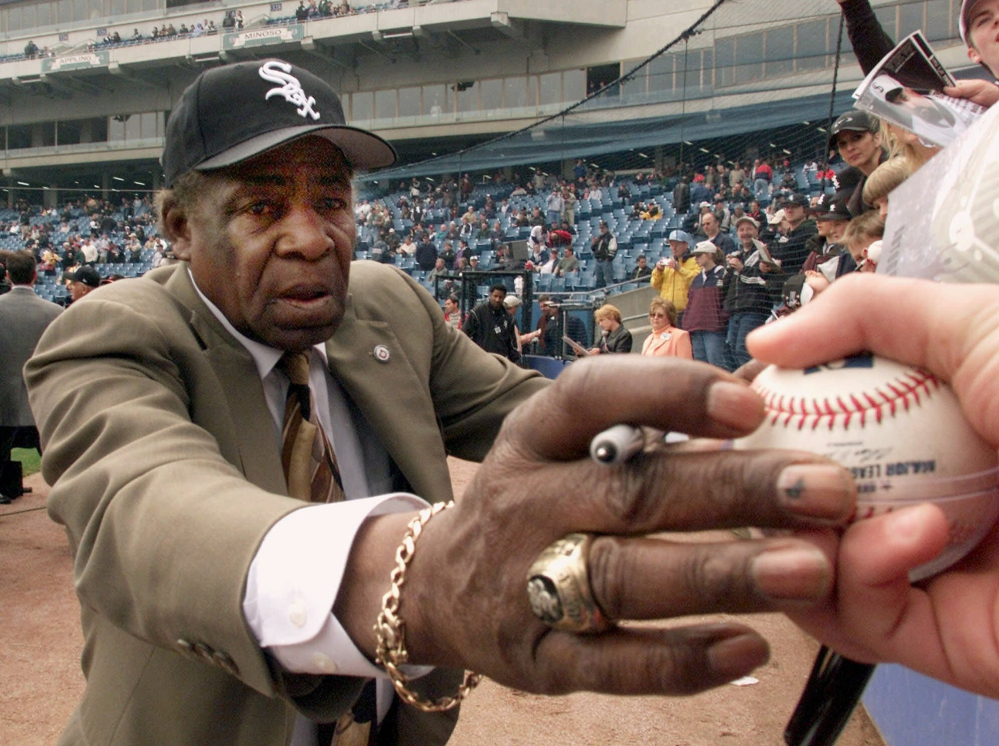 """Chicago White Sox legend Orestes """"Minnie"""" Minoso signs autographs before to the White Sox' home opener against the Detroit Tigers in 2001."""