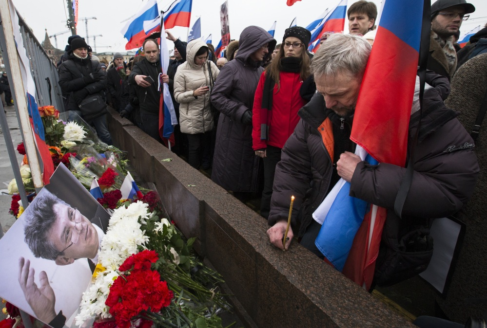 A man cradles a Russian national flag and lights a candle Sunday at the place where Boris Nemtsov, a charismatic Russian opposition leader and sharp critic of President Vladimir Putin, was gunned down on Friday near the Kremlin, in Moscow.