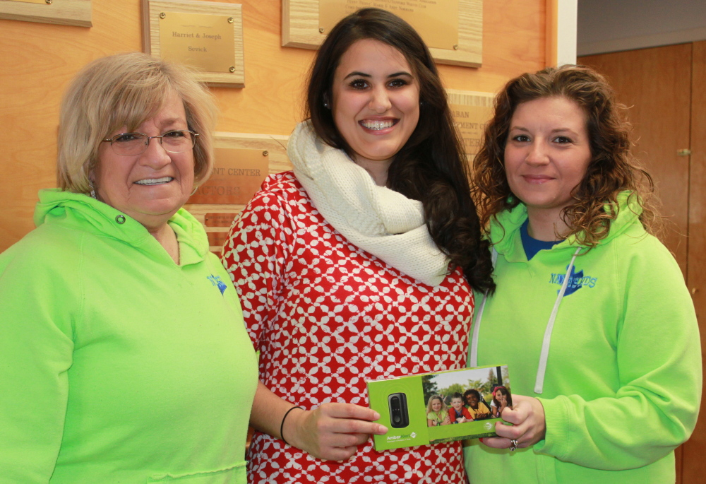 """Donna """"Nana"""" Green, left, and Jessica Lee, right, of Nana's Kids of York present Sarah Mehlhorn of the Fraser-Ford Child Development Center in Sanford with an Amber Alert GPS unit to benefit a child with autism."""