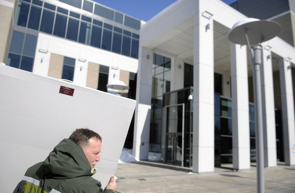 Augusta lawyer Jim Billings carries a photograph of members of the Kennebec County bar into the new Capital Judicial Center in Augusta last week.