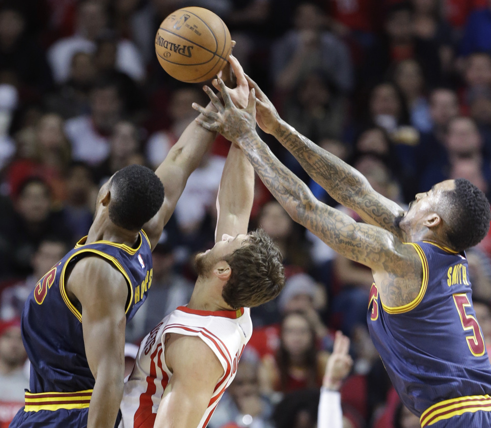 Houston's Donatas Motiejunas is sandwiched between Cleveland's Tristan Thompson, left, and J.R. Smith during the Rockets' 105-103 win in overtime Sunday in Houston.